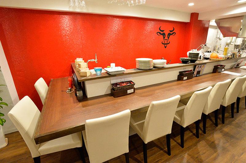 ゆったりしたカウンター席でお食事を<br>赤い壁とオリジナルマークが店名を象徴